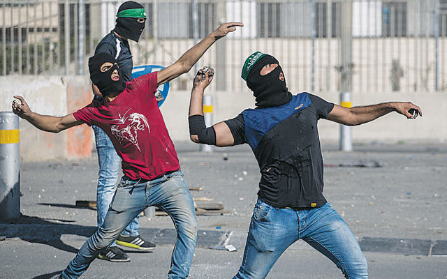 Palestinians throw rocks at Israeli police during clashes in eastern Jerusalem on September 18. (Hadas Parush/Flash90)