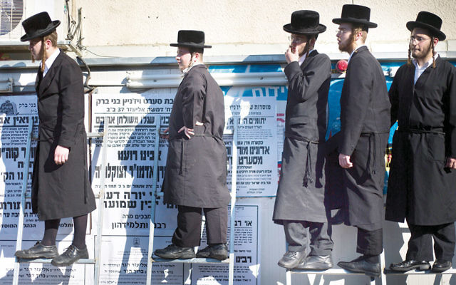 Charedi Orthodox Jews in Israel watch the funeral procession of the prominent Rabbi Eliezer Hager in Haifa on July 8. (Ariel Schalit/AP)