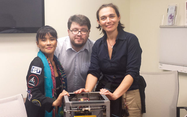 Sheyna Gifford, right, looks at a 3D printer with scientists Dr. Susan Jewell and Matteo Borri. (Courtesy Sheyna Gifford)