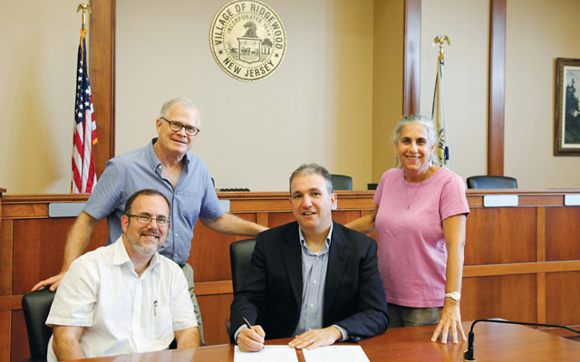 Seated, from left, Rabbi David Fine and Mayor Paul Aronsohn, and standing, from left, Leigh Brown and Johanna Resnick Rosen, all of Ridgewood, as Mr. Aronsohn signs the letter.