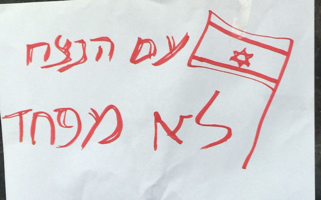 """This sign — """"the eternal people are not afraid"""" — was taped on a Jerusalem bus stop."""