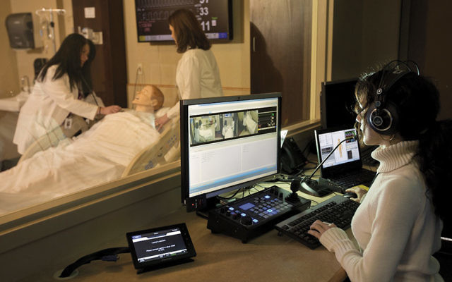 """Nurse Janine Canecchia controls simulation technology while participants treat a """"patient"""" experiencing chest pain during Emergency Response Team training at Holy Name."""