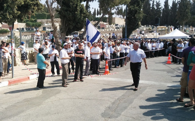 Mourners wait outside Har Hamenuchot during the funeral of Naama and Eitam Henkin last Friday. (Abigail Klein Leichman)