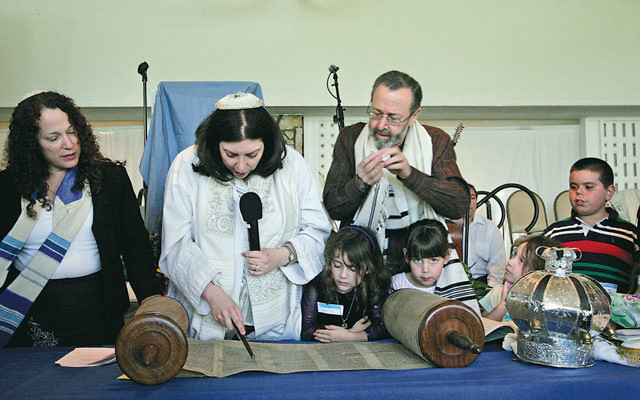 Rabbi Orenstein reads Torah surrounded by members of her California shul, Makom Ohr Shalom, before she moved back to New Jersey.