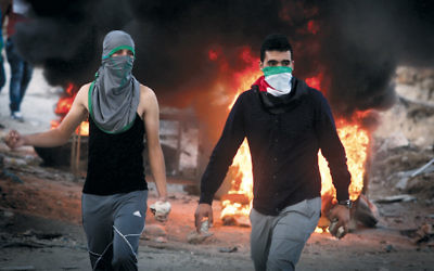 Palestinian protesters in the West Bank throw stones and burn tires during clashes with Israeli security forces over the Al-Aqsa mosque compound on September 30. (Flash90)