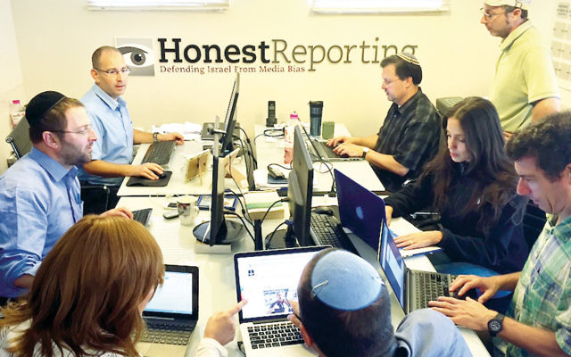 Simon Plosker, top left, managing editor of HonestReporting.com, directs the monitoring team at his organization's Jerusalem headquarters on October 13. (Joe Hyams/HonestReporting)