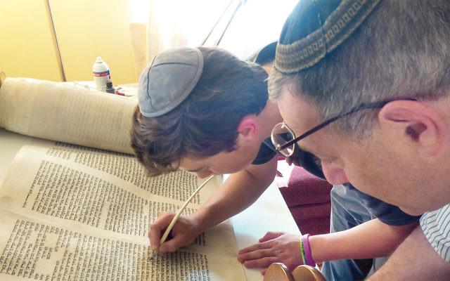 David Gellis inks the Torah scroll while the scribe looks on.