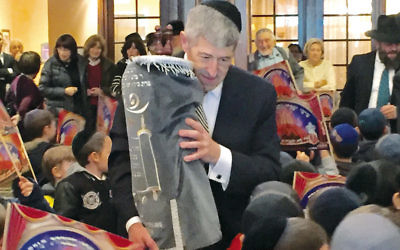 Rabbi Yerachmiel Seplowitz  marched it through the lobby in celebration. (Courtesy FountainView)