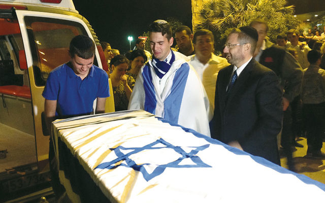 Some of Ezra Schwartz's many friends mourn over the coffin of the American terror victim at a service at Ben Gurion Airport in Israel before the body was repatriated to Boston for his funeral the following day, November 21. (JTA/Ben Sales)