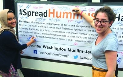 """Spread Hummus Not Hate"" organizer Symi Rom-Rymer signs a pledge of peace with a Muslim student from the University of Maryland."