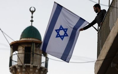An Israeli Jews raises a flag near the Old City of Jerusalem. The number of Jewish residents in the Old City and predominantly Arab areas nearby has increased 40 percent since 2009. (Abir Sultan/Flash 90)