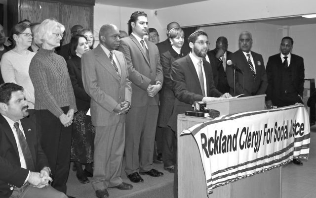 Members of Rockland Clergy for Society Justice are together at a rally. Rabbi Ari Hart of the Hebrew Institute of Riverdale speaks; Rabbi Paula Mack Drill stands directly behind him. Rabbi Michael S. Churgel of the Reform Temple of Rockland sits at the far left. The three rabbis are, respectively, Orthodox, Conservative, and Reform. (Katrina Hertzberg)