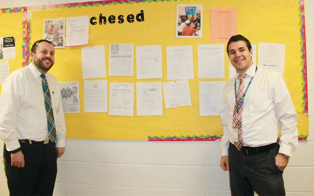 Rabbi Eitan Lipstein, left, and Rabbi Yoni Fein with the Moriah chesed board.