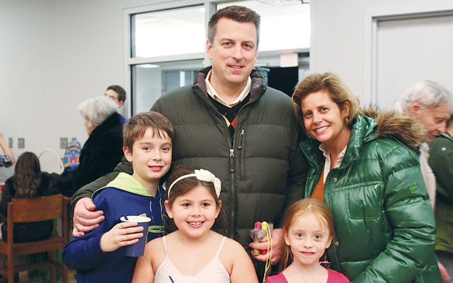 David and Elizabeth Lewison and their children, Ethan and Bridget, are pictured with a friend, Claudia Dojknik, right, front row, at last year's River Vale Chanukah celebration. (Courtesy Valley Chabad)