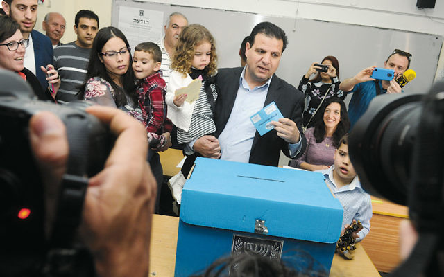 Ayman Odeh, carrying one of his three children, casts his vote in Nazareth on March 17. (Basal Awidat/Flash90)