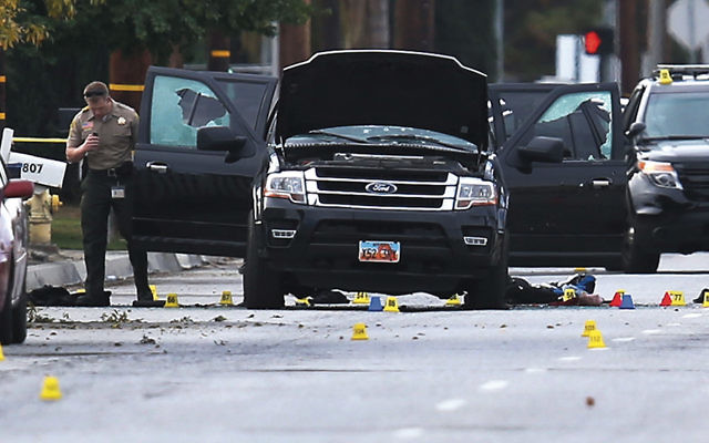 Law enforcement officials investigate the Ford SUV at the scene where suspects of the shooting at the Inland Regional Center in San Bernardino, Calif., were killed in a shootout with police on December 3. (Joe Raedle/Getty Images)