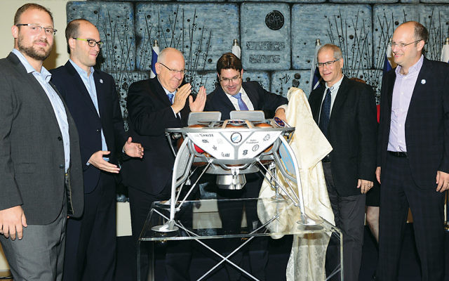 Israel's President Reuven Rivlin, center left, is among the onlookers as the spacecraft prototype is unveiled. Alon Hadar