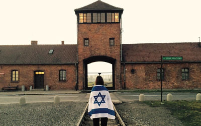 Wrapped in an Israeli flag, Alexa Hirschberg stands outside the gates of Auschwitz.