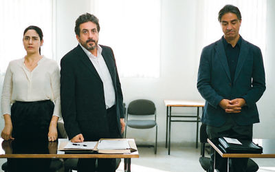 "In this still from ""Gett: The Trial of Viviane Amsalem,"" Viviane, played by director Ronit Elkabetz, stands next to her lawyer, played by Menashe Noy. Her husband, played by Simon Abkarian, stands alone."
