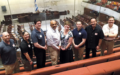 From left, Lafe Bush, Cathy Madalone, John Devine, Dr. James Pruden, Jacqueline Luthcke, Todd Pearl, Timothy Torell, and Kenneth Ehrenberg stand in a gallery at the Knesset.