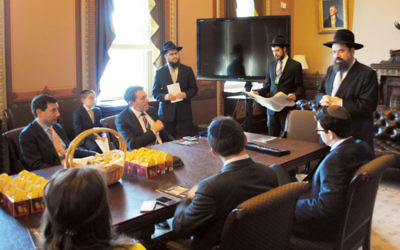 Matt Nosanchuk, seated at the end of table, facing out, at a Purim megillah reading in the White House's diplomatic reception room on March 24.