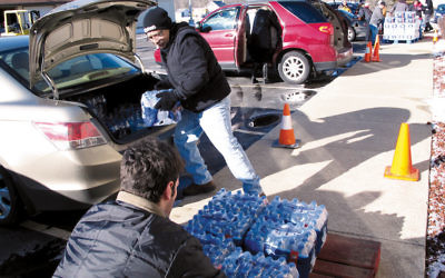Volunteers offload bottled water donated by the Flint Jewish community to a local church as the lead crisis in the water supply continued. (Courtesy of Flint Jewish Federation)