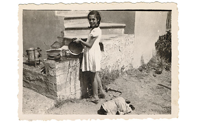 Young Johanna Neumann washing dishes outdoors in Shkoset, Albania.
