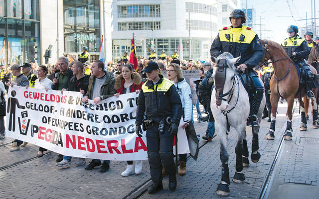 Demonstrators protest the arrival of Muslim immigrants to Europe in the Hague, Netherlands, on April 10. (Cnaan Liphshiz)