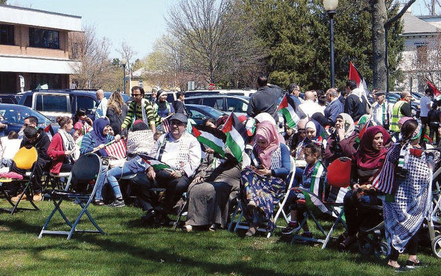 A crowd watches the Palestinian flag, inset, being raised in Clifton.