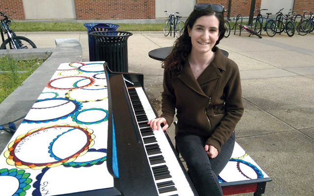 Keren Straus of Teaneck, a junior at the University of Maryland, shows her custom-painted piano, which will be donated to the Jewish Home Assisted Living.