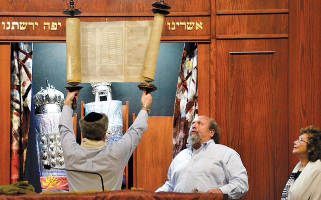 A CBI congregant, left, raises a rescued Holocaust Torah during a Yom HaShoah ceremony. Cantor Lenny Mandel is with him.