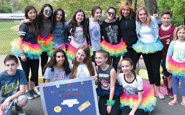 """The """"Tutus"""" are taking Tenafly once again to help support individuals with special needs in the community!  Spotted this weekend, they were raising some last-minute funds for the Rubin Run, selling lemonade in their rainbow tutus. Suzette Josif, Rubin Run co-chair, is standing with her two daughters and son by her side."""