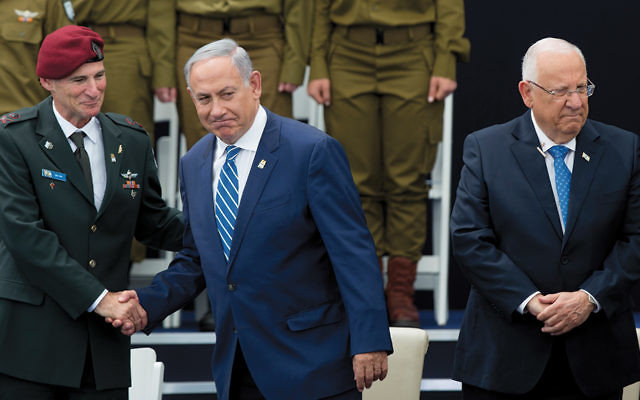 Prime Minister Benjamin Netanyahu, center, shakes hands with Deputy IDF Chief of Staff Yair Golan as he stands with President Reuven Rivlin at an Israeli Independence Day ceremony honoring soldiers on May 12. (Yonatan Sindel/Flash90)