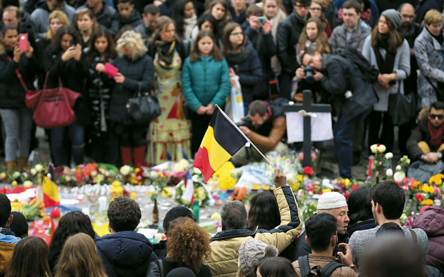 Belgians look at tributes to the victims of the March 22 terrorist attack at the Brussels airport. The gathering in the Place De La Bourse occurred the day after the attack. (Christopher Furlong/Getty Images)