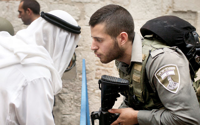 An Israeli border policeman talks to a Palestinian man near the scene of a stabbing attack in Jerusalem's Old City last October. (Lior Mizrahi/Getty Images)