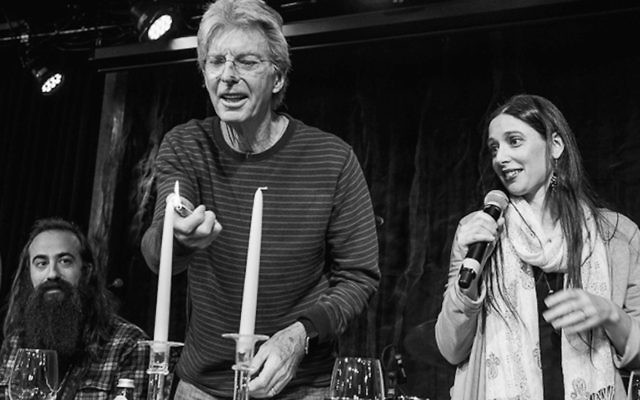 Phil Lesh lights the candles as Jeannette Ferber sings the blessing and guitarist Ross James looks on. (© Bob Minkin Photography/www.minkinphotography.com)