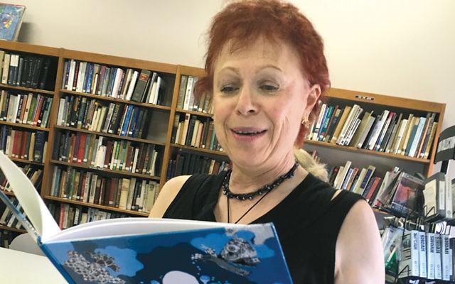 "Susan Levin looks at ""Das Fligeleh Un Ber"" in Temple Emeth's library."