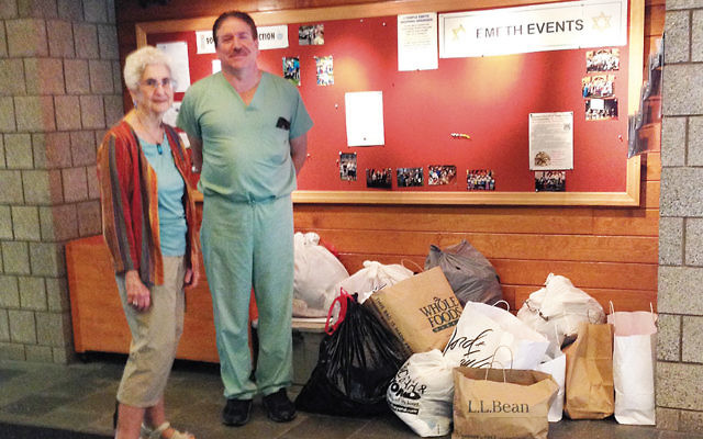 Eva Sandrof, co-chair of Temple Emeth's social action committee, and Dr. Sam Carr with clothing collected for seniors.