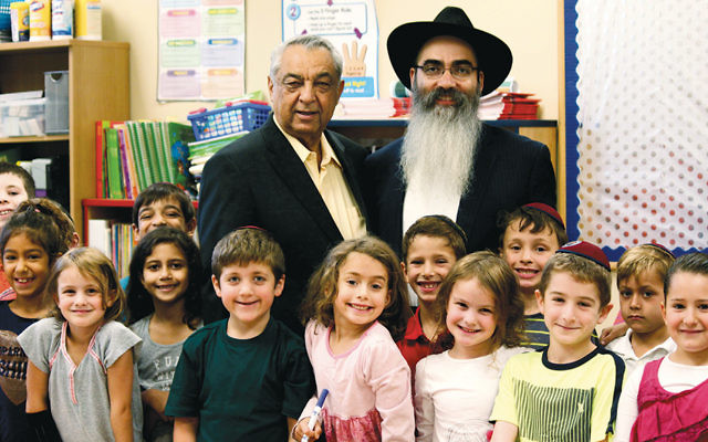 Rabbi Mordechai Shain, right, and Joshua Lapsker of Tenafly are surrounded by students at Lubavitch on the Palisades elementary school.