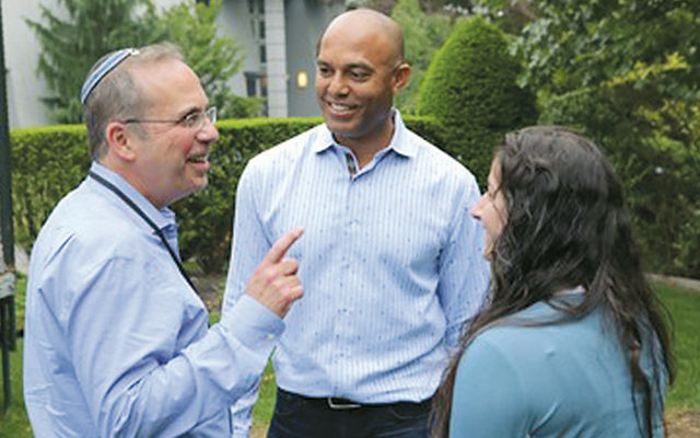 Robert Katz of Fair Lawn, Ohel's chief development officer, with Mariano Rivera and one of his fans. (Photo courtesy Ohel)