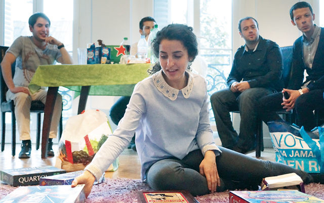 Noemie Grausz shows the board games to her guests at Moishe House Beaubourg in Paris last month. (Cnaan Liphshiz)