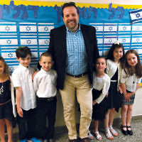 Rabbi David-Seth Kirshner of Temple Emanu-El of Closter at Solomon Schechter Day School of Bergen County's first grade Kabbalat Siddur ceremony, with shul members and their friends. From left, Talya Schwartzbard, Eli Nanus, Harrison Cohen, Sophie Gutter, Lauren Messer, and Jordan Masdorf. Rabbi Kirshner is also a SSDS board member. (Courtesy Temple Emanu-El)