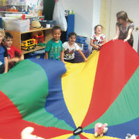 "Campers at Gan Yaldenu in Teaneck had the chance for parachute play with their stuffed bears for ""Bears Week."" (Courtesy Gan Yaldenu)"