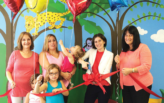 From left, Debbie Wanamaker, the director of the parenting center at Temple Emanuel; Liz Sagat of Woodcliff Lake; Rabbi Loren Monosov; and shul president Susan Bromberg stand with Ms. Sagat's three daughters as Rabbi Monosov cuts the ribbon.
