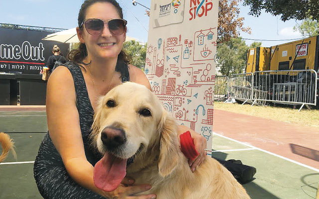 Mira Marcus, the city of Tel Aviv's director of international press, with her dog, Shani, at the festival. (Andrew Tobin)