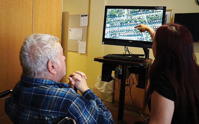 A JHR resident reminisces about his childhood neighborhood while viewing it with JHR recreation leader Daisy Tantay using one of the iN2L units she brought to his room. (Jewish Home Family)