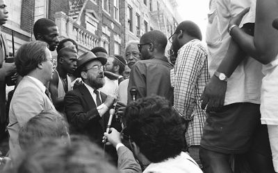 New York City Mayor David Dinkins, fourth from right, looking on while a chasidic Jew and a black man argue during riots in Crown Heights, Brooklyn, in 1991. (Anthony Pescatore/NY Daily News Archive via Getty Images)