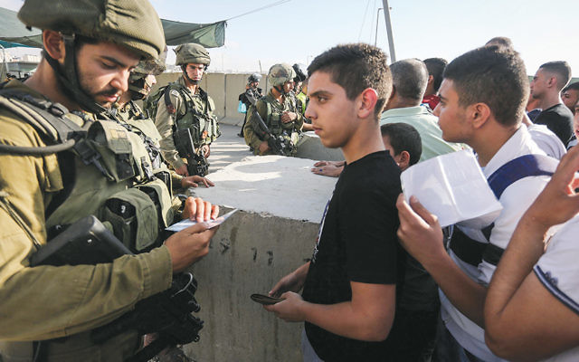 Israeli soldiers check Palestinian IDs at the Qalandia checkpoint between the West Bank city of Ramallah and Jerusalem on July 1. (Flash90)