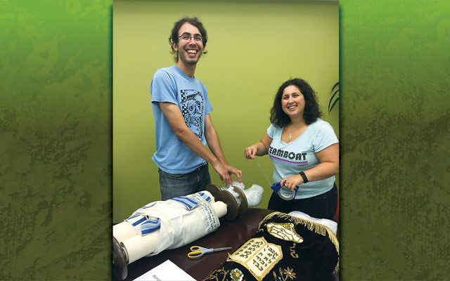 Project Kesher's associate director of development and marketing, Kimmie Braunthal, and Kesher volunteer Ben Orenstein prepare Torah scrolls for their trip to new homes in Eastern Europe.