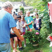 """Temple Emeth congregant Paul Rubock helps the Teaneck shul's religious school students plant hydrangea bushes to commemorate the 15th anniversary of the 9/11 attacks. Afterward, there was a service led by Teaneck Mayor  Mohamed Hamaduddin; participants included Councilman Alan Sohn and Rabbi Steven Sirbu. Louis Santos played """"Taps"""" on his trumpet. Afterward, a group helped to clean up Windsor Park. (Carla Silver)"""